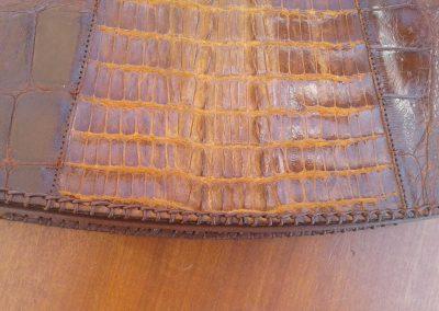 Couture sur un sac cuir croco en restauration